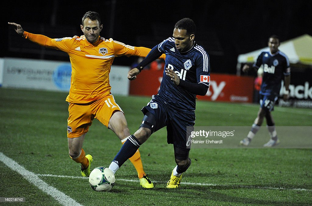 Brad Davis #11 of the Houston Dynamo and <a gi-track='captionPersonalityLinkClicked' href=/galleries/search?phrase=Matt+Watson+-+Soccer+Player&family=editorial&specificpeople=15003259 ng-click='$event.stopPropagation()'>Matt Watson</a> #8 of the Vancouver Whitecaps FC battle for the ball during the second half of a game at Blackbaud Stadium on February 20, 2013 in Charleston, North Carolina.