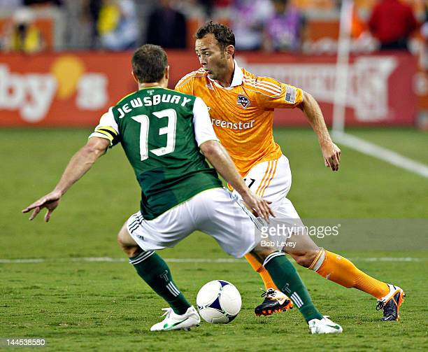 Brad Davis of the Houston Dynamo moves past Jack Jewsbury of the Portland Timbers in the first half at BBVA Compass Stadium on May 15 2012 in Houston...