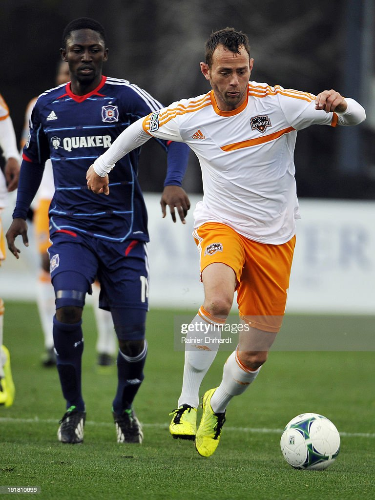 Brad Davis #11 of the Houston Dynamo runs with the ball as <a gi-track='captionPersonalityLinkClicked' href=/galleries/search?phrase=Patrick+Nyarko&family=editorial&specificpeople=4824163 ng-click='$event.stopPropagation()'>Patrick Nyarko</a> #14 of the Chicago Fire defends during the first half of their game in the Carolina Challenge Cup at Blackbaud Stadium on February 16, 2013 in Charleston, South Carolina.