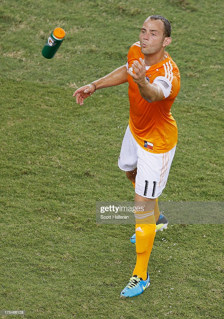 Brad Davis #11 of the Houston Dynamo tosses a water bottle during the game against the Chicago Fire at BBVA Compass Stadium on July 27, 2013 in Houston, Texas.