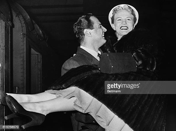 Brad Dexter is carrying his pretty wife movie star Peggy Lee in the approved manner for crossing thresholds as they arrive in New York today Miss Lee...