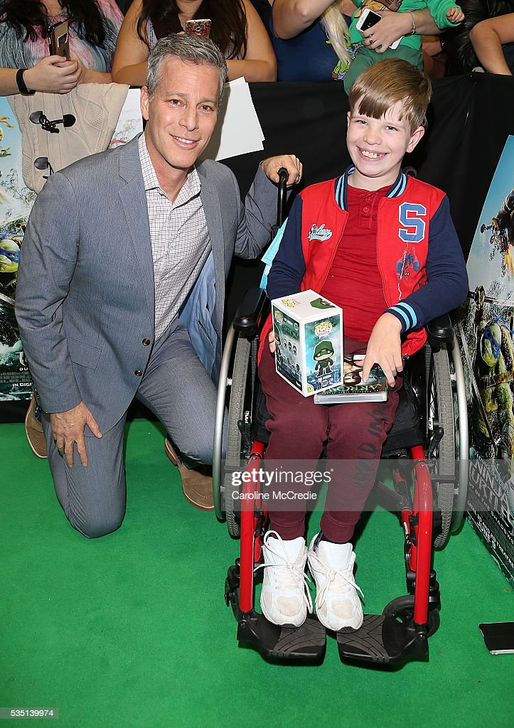 Brad Fuller poses with a fan ahead of the Australian premiere of Teenage Mutant Ninja Turtles 2 at Event Cinemas George Street on May 29, 2016 in Sydney, Australia.