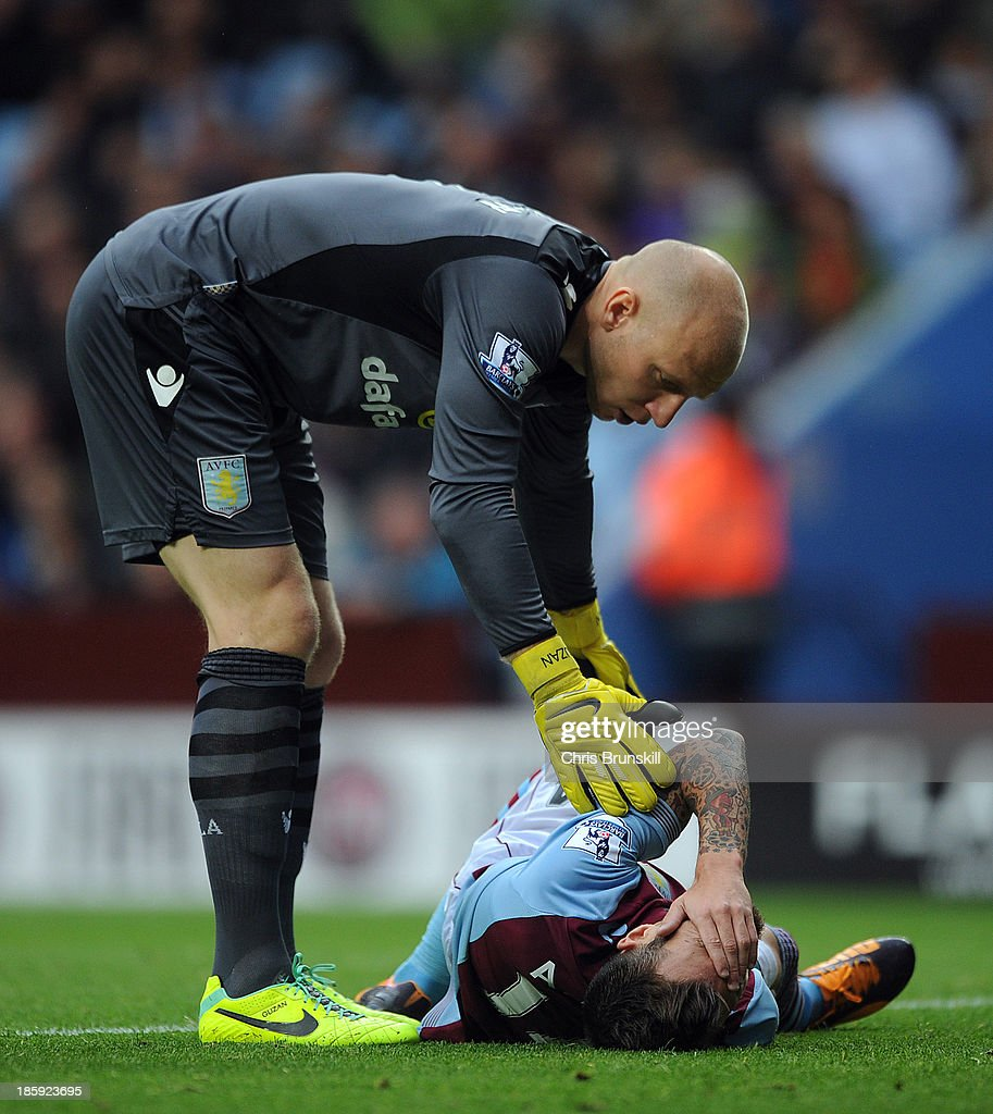 Brad Guzan of Aston Villa checks on injured team-mate Antonio Luna during the Barclays Premier League match between Aston Villa and Everton at Villa Park on October 26, 2013 in Birmingham, England.