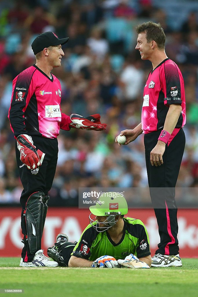 Brad Haddin and Brett Lee of the Sixers share a laugh as Ryan Carters of the Thunder lies on the ground during the Big Bash League match between Sydney Thunder and the Sydney Sixers at ANZ Stadium on December 30, 2012 in Sydney, Australia.