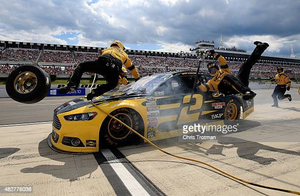 Brad Keselowski driver of the Alliance Truck Parts Ford crashes into his crew on pit road during the NASCAR Sprint Cup Series Windows 10 400 at...