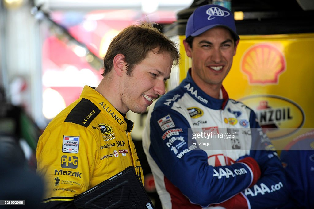 Brad Keselowski, driver of the #2 Alliance Truck Parts Ford, speaks with Joey Logano, driver of the #22 AAA Ford, during practice for the NASCAR Sprint Cup Series Go Bowling 400 at Kansas Speedway on May 6, 2016 in Kansas City, Kansas.