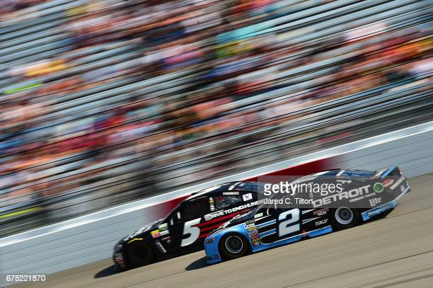 Brad Keselowski driver of the Detroit Genuine Parts Ford races Kasey Kahne driver of the AARP Drive to End Hunger Chevrolet during the Monster Energy...