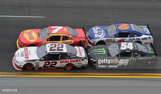 Brad Keselowski driver of the Discount Tire Ford and Regan Smith driver of the Ragu Chevrolet race ahead of Kyle Busch driver of the Monster Energy...