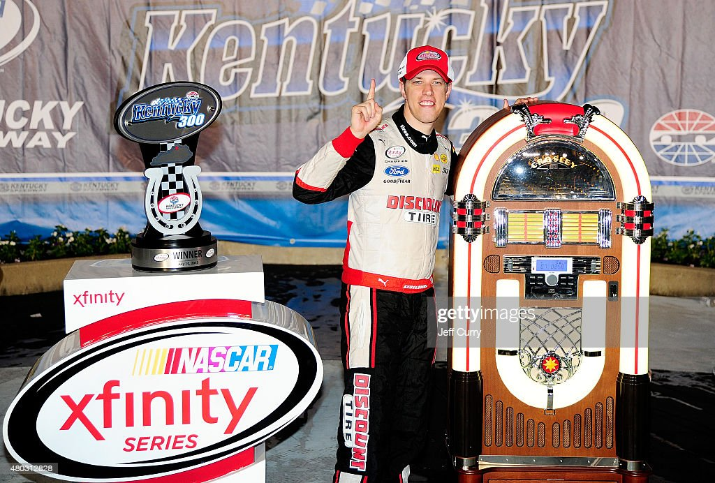 Brad Keselowski, driver of the #22 Discount Tire Ford, poses with the winner's trophy and commemorative juke box in Victory Lane after winning the NASCAR XFINITY Series Kentucky 300 at Kentucky Speedway on July 10, 2015 in Sparta, Kentucky.