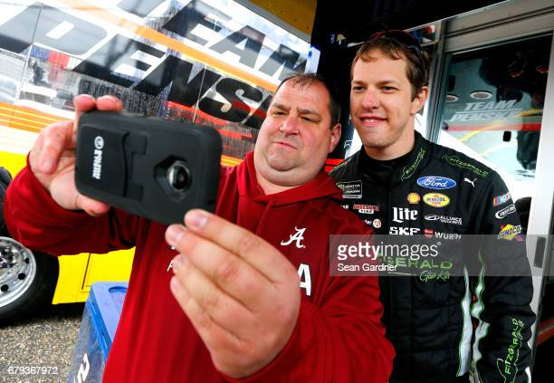 Brad Keselowski driver of the Fitzgerald Glider Kits Ford takes a photo with a fan during practice for the Monster Energy NASCAR Cup Series GEICO 500...