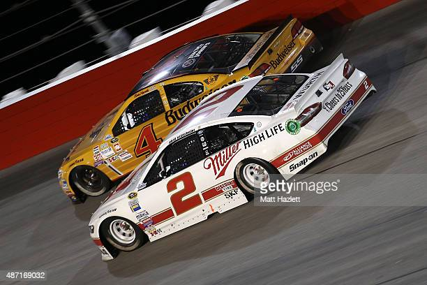 Brad Keselowski driver of the Miller High Life Ford races Kevin Harvick driver of the Budweiser/Jimmy John's Chevrolet during the NASCAR Sprint Cup...