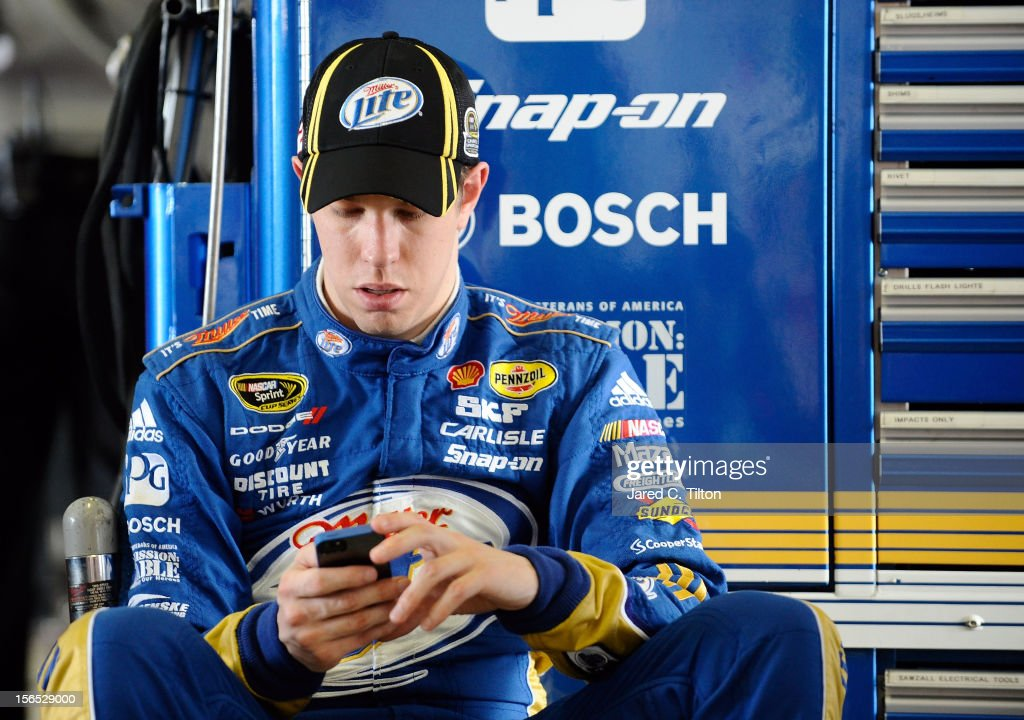 Brad Keselowski, driver of the #2 Miller Lite Dodge, uses his smartphone in the garage area during practice for the NASCAR Sprint Cup Series Ford EcoBoost 400 at Homestead-Miami Speedway on November 16, 2012 in Homestead, Florida.