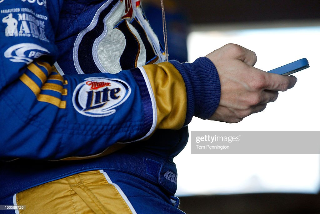 Brad Keselowski, driver of the #2 Miller Lite Dodge, uses his Smartphone in the garage during practice for the NASCAR Sprint Cup Series Ford EcoBoost 400 at Homestead-Miami Speedway on November 17, 2012 in Homestead, Florida.