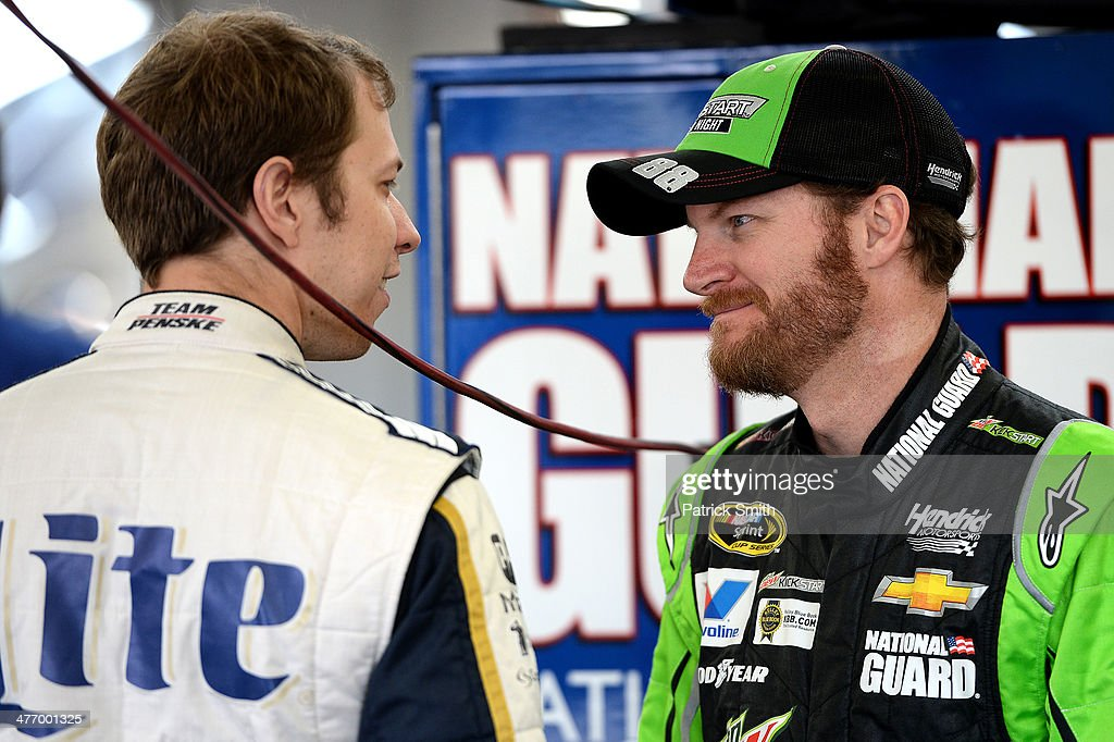 Brad Keselowski, driver of the #2 Miller Lite Ford, (L) and Dale Earnhardt Jr., driver of the #88 Mountain Dew Kickstart Chevrolet, talk to one another during NASCAR Sprint Cup Series testing at Las Vegas Motor Speedway on March 6, 2014 in Las Vegas, Nevada.
