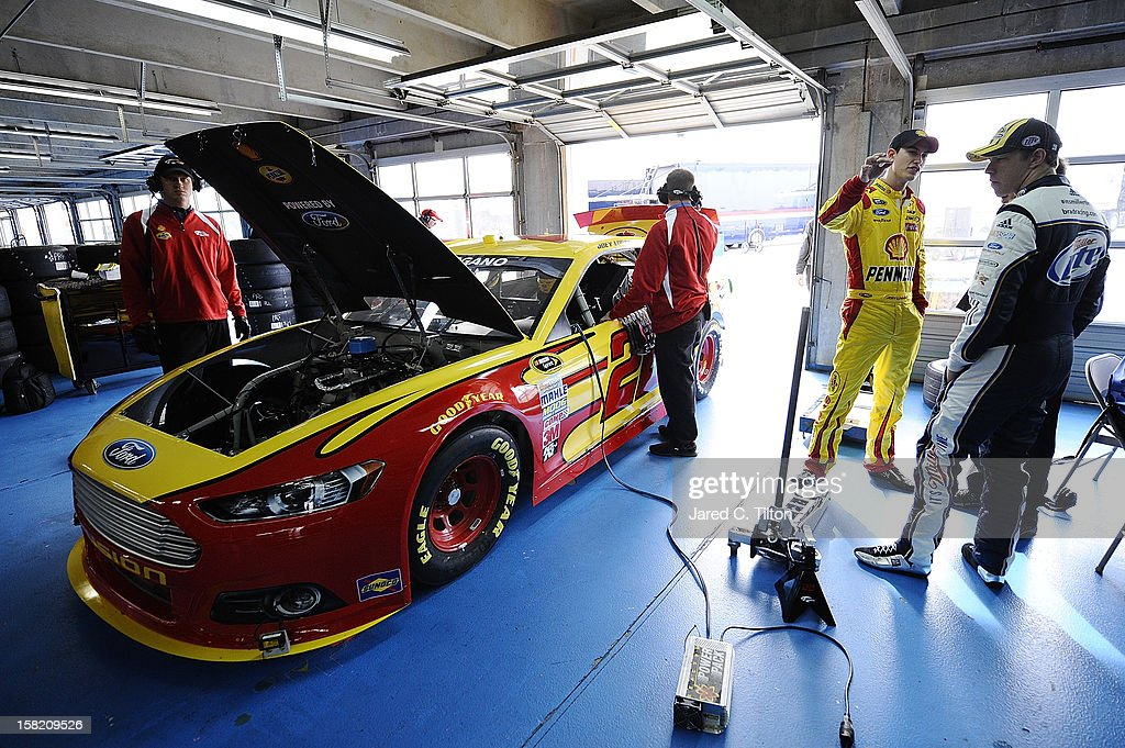 Brad Keselowski (R), driver of the #2 Miller Lite Ford, and Joey Logano, driver of the #22 Shell/Pennzoil Ford, talk in the garage area during testing at Charlotte Motor Speedway on December 11, 2012 in Concord, North Carolina.