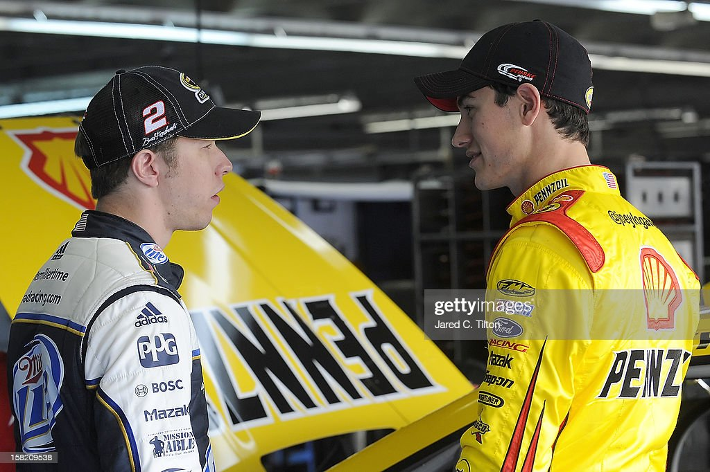 Brad Keselowski (L), driver of the #2 Miller Lite Ford, and Joey Logano, driver of the #22 Shell/Pennzoil Ford, talk in the garage area during testing at Charlotte Motor Speedway on December 11, 2012 in Concord, North Carolina.