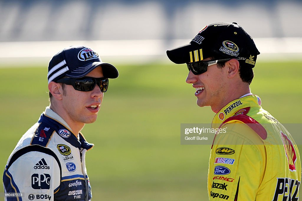 Brad Keselowski, driver of the #2 Miller Lite Ford, and Joey Logano, driver of the #22 Shell-Pennzoil Ford, speak on pit road during qualifying for the NASCAR Sprint Cup Series Geico 400 at Chicagoland Speedway on September 13, 2013 in Joliet, Illinois.