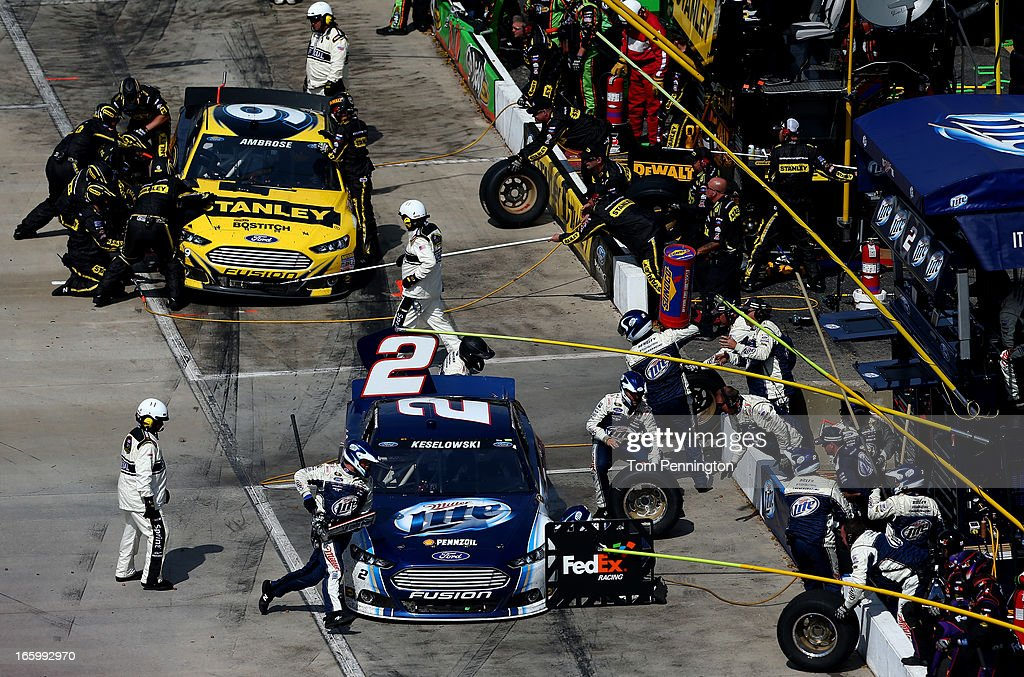 Brad Keselowski, driver of the #2 Miller Lite Ford, and Marcos Ambrose, driver of the #9 Stanley Ford, make a pit stop during the NASCAR Sprint Cup Series STP Gas Booster 500 on April 7, 2013 at Martinsville Speedway in Ridgeway, Virginia.