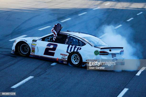 Brad Keselowski driver of the Miller Lite Ford celebrates after winning the Monster Energy NASCAR Cup Series STP 500 at Martinsville Speedway on...