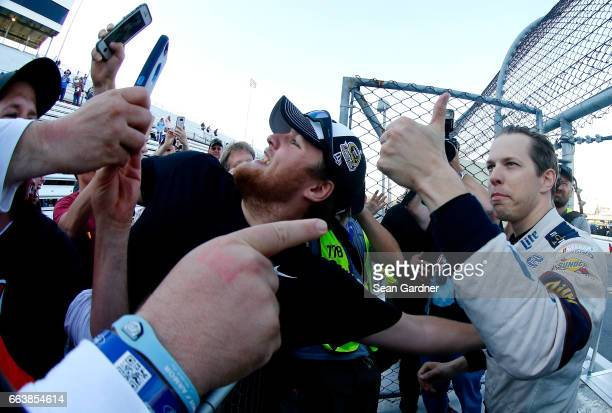 Brad Keselowski driver of the Miller Lite Ford celebrates in the grandstands after winning the Monster Energy NASCAR Cup Series STP 500 at...