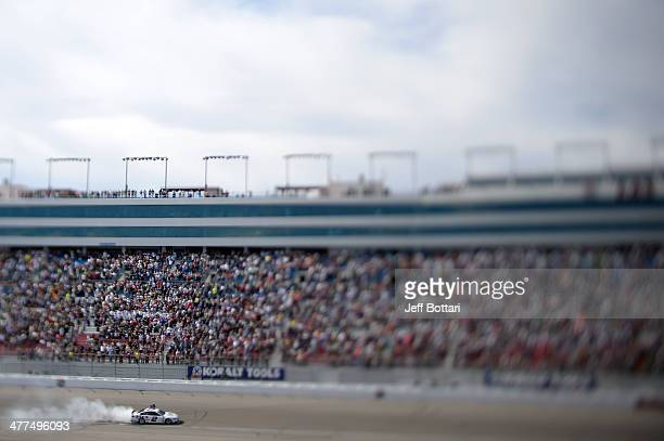 Brad Keselowski driver of the Miller Lite Ford celebrates with a burnout after winning the NASCAR Sprint Cup Series Kobalt 400 at Las Vegas Motor...