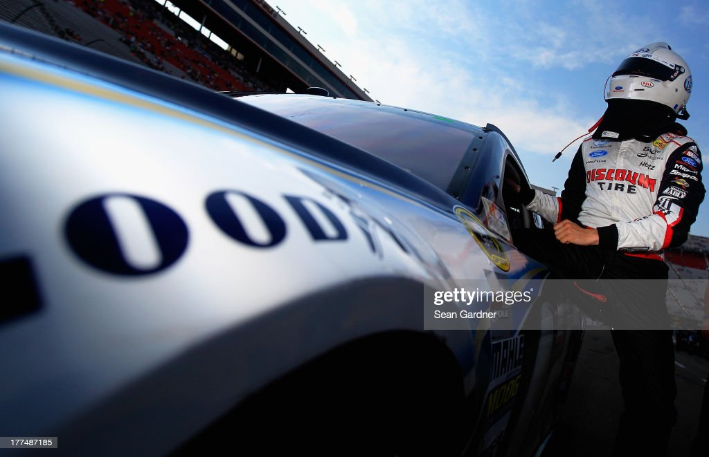 Brad Keselowski, driver of the #2 Miller Lite Ford, climbs from his car after qualifying for the NASCAR Sprint Cup Series IRWIN Tools Night Race at Bristol Motor Speedway on August 23, 2013 in Bristol, Tennessee.