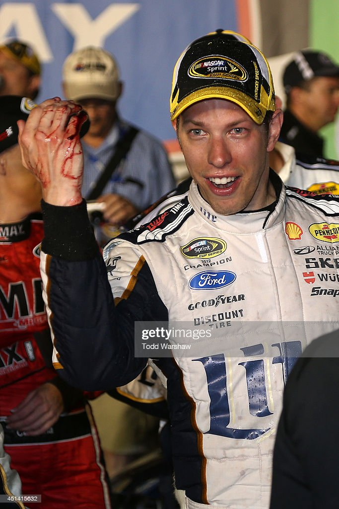 <a gi-track='captionPersonalityLinkClicked' href=/galleries/search?phrase=Brad+Keselowski&family=editorial&specificpeople=890258 ng-click='$event.stopPropagation()'>Brad Keselowski</a>, driver of the #2 Miller Lite Ford, cut his hand on a champagne bottle while celebrating in Victory Lane after winning the NASCAR Sprint Cup Series Quaker State 400 presented by Advance Auto Parts at Kentucky Speedway on June 28, 2014 in Sparta, Kentucky.