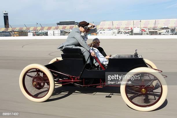 Brad Keselowski driver of the Miller Lite Ford drives a 1901 Sweepstakes exact replica on track with NBC's Kelli Stavast befoe practice for the...