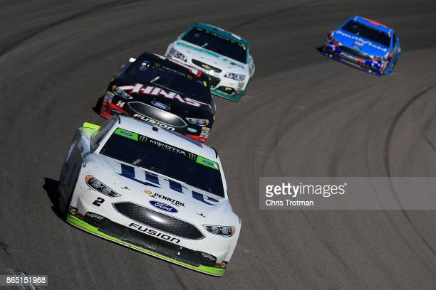 Brad Keselowski driver of the Miller Lite Ford leads Clint Bowyer driver of the Haas Automation Ford Kasey Kahne driver of the UniFirst Chevrolet and...