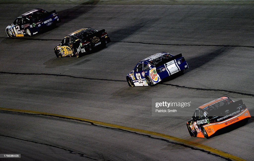 Brad Keselowski, driver of the #2 Miller Lite Ford, leads JJ Yeley, driver of the #36 United Mining Equipment Chevrolet, Travis Kvapil, driver of the #93 Burger King/Dr. Pepper Toyota, and Clint Bowyer, driver of the #15 RKMotorsCharlotte.com Toyota, during the NASCAR Sprint Cup Series AdvoCare 500 at Atlanta Motor Speedway on September 1, 2013 in Hampton, Georgia.