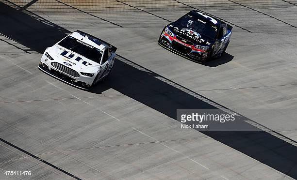 Brad Keselowski driver of the Miller Lite Ford leads Kasey Kahne driver of the Farmers Insurance Chevrolet during the NASCAR Sprint Cup Series FedEx...