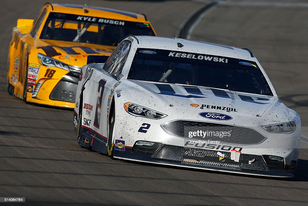 Brad Keselowski driver of the Miller Lite Ford leads Kyle Busch driver of the MM's 75 Toyota at the end of the NASCAR Sprint Cup Series Kobalt 400 at...