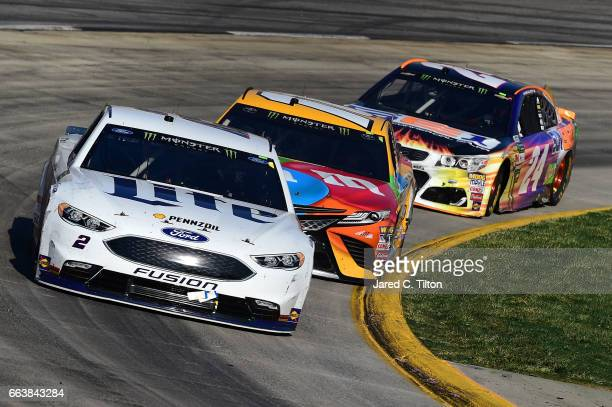Brad Keselowski driver of the Miller Lite Ford leads Kyle Busch driver of the MM's Toyota and Chase Elliott driver of the SunEnergy1 Chevrolet during...
