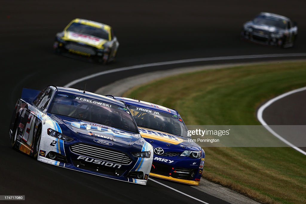 Brad Keselowski, driver of the #2 Miller Lite Ford, leads Martin Truex Jr., driver of the #56 NAPA Auto Parts Toyota, Greg Biffle, driver of the #16 3M Safety Ford, and Jimmie Johnson, driver of the #48 Lowe's/Kobalt Tools Chevrolet, during the NASCAR Sprint Cup Series Samuel Deeds 400 At The Brickyard at Indianapolis Motor Speedway on July 28, 2013 in Indianapolis, Indiana.