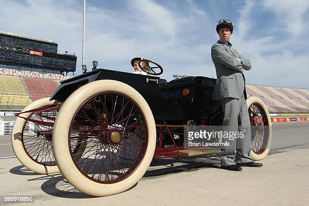 Brad Keselowski driver of the Miller Lite Ford poses with a 1901 Sweepstakes exact replica on track before practice for the NASCAR Sprint Cup Series...