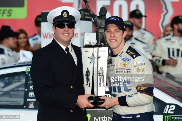 Brad Keselowski driver of the Miller Lite Ford poses with the trophy in victory lane after winning the Monster Energy NASCAR Cup Series Alabama 500...