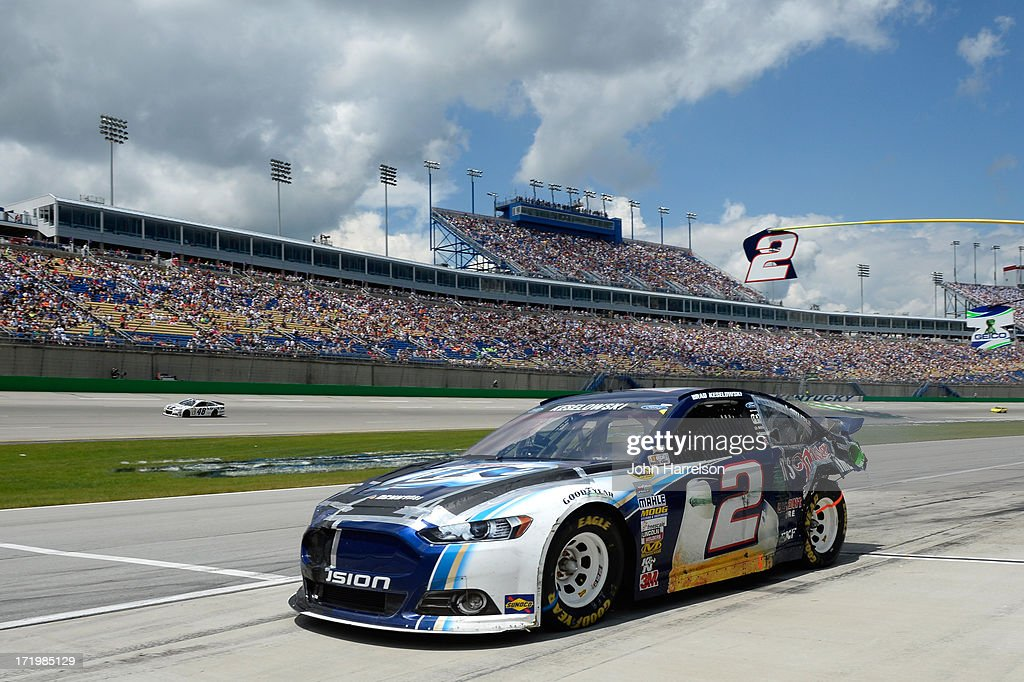 Brad Keselowski, driver of the #2 Miller Lite Ford, pulls out of the garage after repairs as Jimmie Johnson, driver of the #48 Lowe's Dover White Chevrolet, races past during the NASCAR Sprint Cup Series Quaker State 400 at Kentucky Speedway on June 30, 2013 in Sparta, Kentucky.