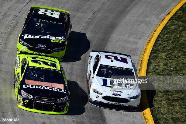 Brad Keselowski driver of the Miller Lite Ford races Paul Menard driver of the Duracell/Menards Chevrolet and Joey Logano driver of the Duralast GT...
