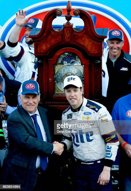 Brad Keselowski driver of the Miller Lite Ford shakes hands with Clay Campbell Martinsville Speedway president after winning the Monster Energy...