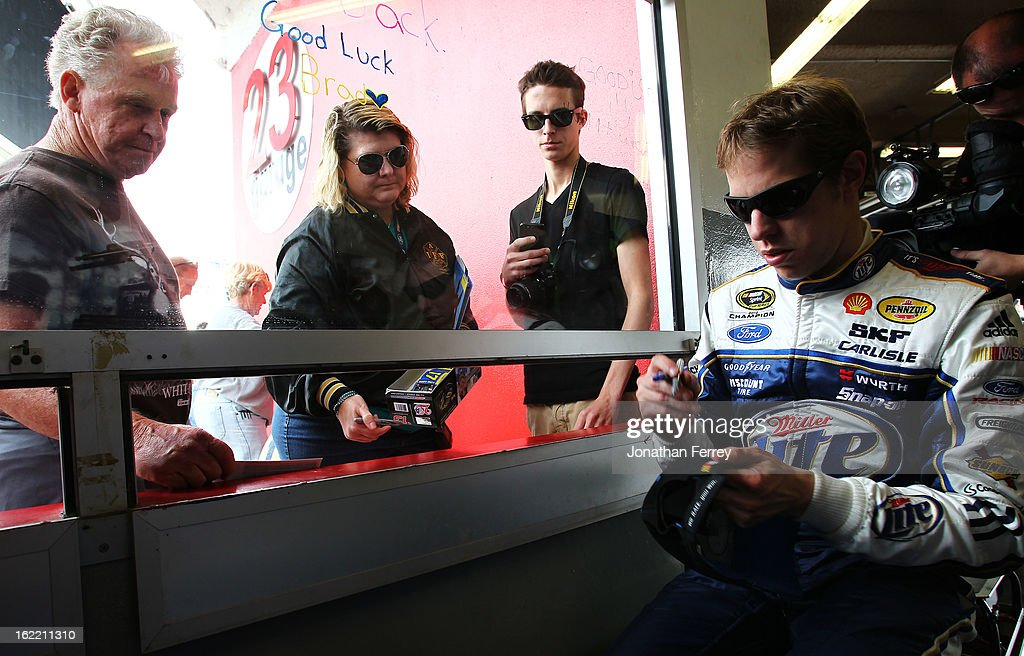 Brad Keselowski, driver of the #2 Miller Lite Ford, signs an autograph in the garage area during practice for the NASCAR Sprint Cup Series Daytona 500 at Daytona International Speedway on February 20, 2013 in Daytona Beach, Florida.