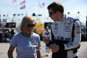 Brad Keselowski driver of the Miller Lite Ford signs autographs during practice for the NASCAR Sprint Cup Series Pure Michigan 400 at Michigan...