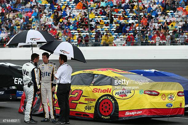 Brad Keselowski driver of the Miller Lite Ford takes cover with his crew chief Paul Wolfe under umbrellas during a rain delay in the NASCAR Sprint...