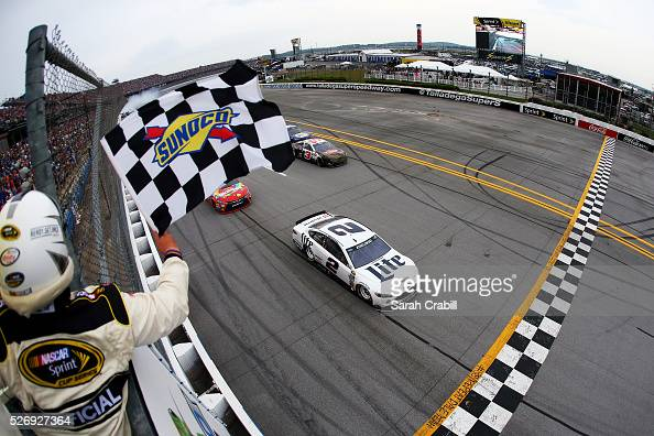 Brad Keselowski driver of the Miller Lite Ford takes the checkered flag to win the NASCAR Sprint Cup Series GEICO 500 at Talladega Superspeedway on...