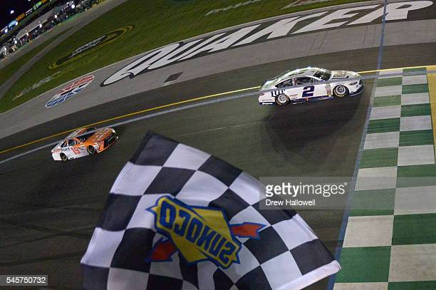Brad Keselowski driver of the Miller Lite Ford takes the checkered flag to win the NASCAR Sprint Cup Series Quaker State 400 at Kentucky Speedway on...