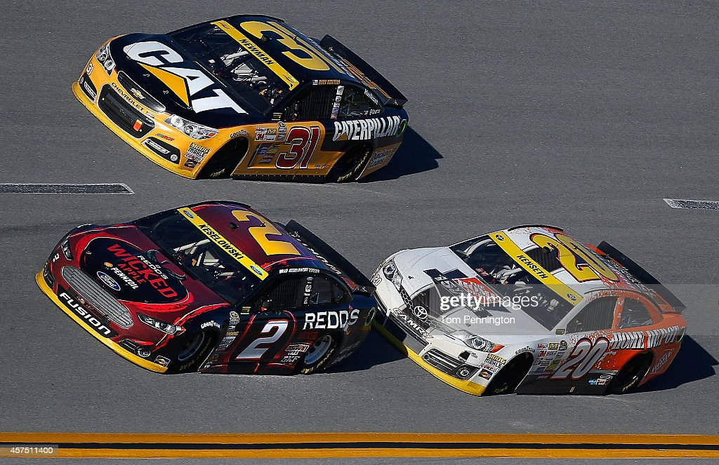 Brad Keselowski driver of the Redd's Wicked Apple Ale Ford leads Ryan Newman driver of the Caterpillar Chevrolet and Matt Kenseth driver of the Home...