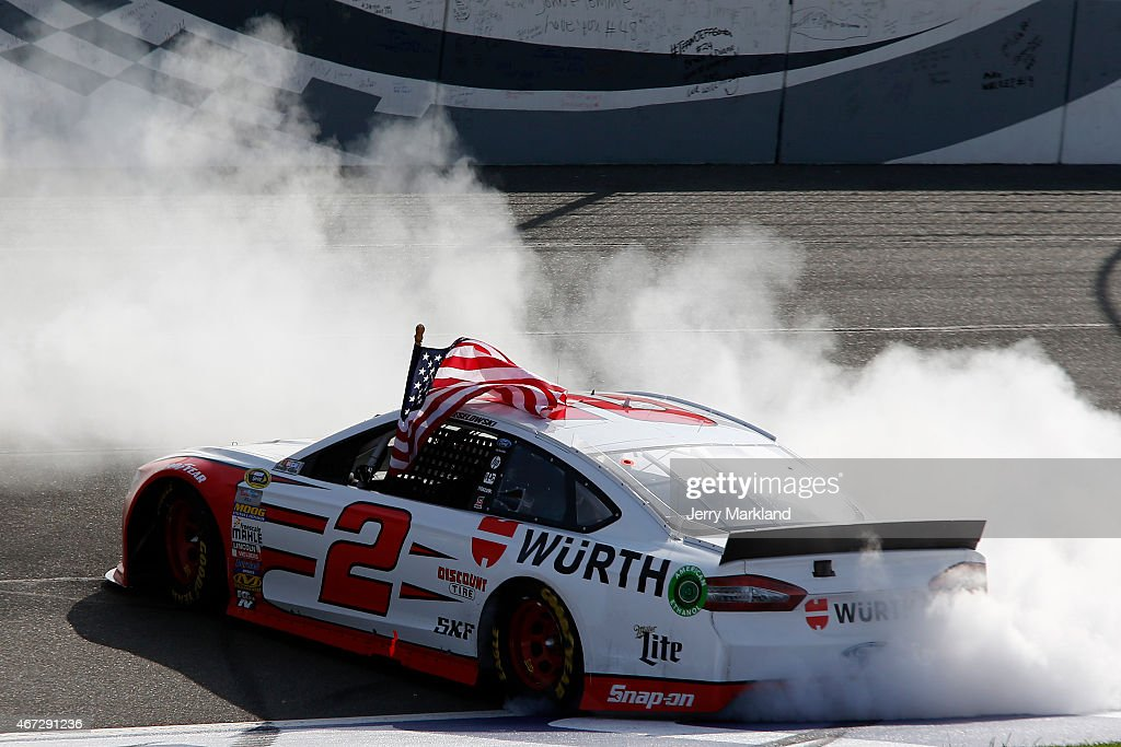 Brad Keselowski driver of the Wurth Ford celebrates with a burnout after winning the NASCAR Sprint Cup Series Auto Club 400 at Auto Club Speedway on...