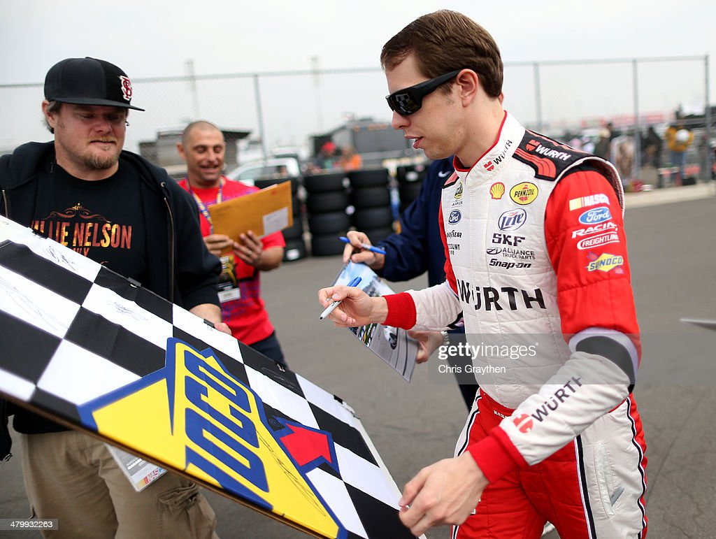 Brad Keselowski, driver of the #2 Wurth Ford, signs an autograph for a fan during practice for the NASCAR Sprint Cup Series Auto Club 400 at Auto Club Speedway on March 21, 2014 in Fontana, California.