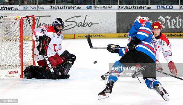 Brad Leeb scores his team's second goal against goalie Scott Travis of Hannover during the fourth DEL quarter final playoff game between Thomas Sabo...