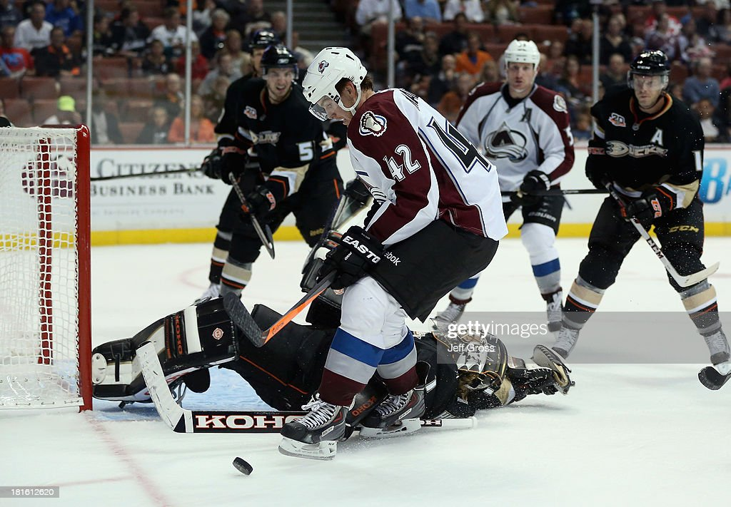 Brad Malone #42 of the Colorado Avalanche tries to control the puck, as goaltender <a gi-track='captionPersonalityLinkClicked' href=/galleries/search?phrase=Jonas+Hiller&family=editorial&specificpeople=743364 ng-click='$event.stopPropagation()'>Jonas Hiller</a> #1 of the Anaheim Ducks sprawls on his back in the second period at Honda Center on September 22, 2013 in Anaheim, California.