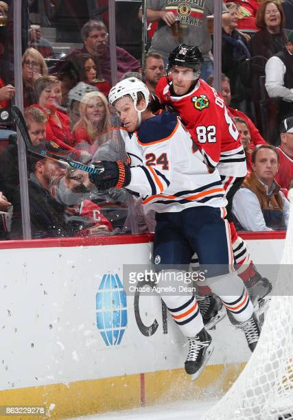 Brad Malone of the Edmonton Oilers and Jordan Oesterle of the Chicago Blackhawks get physical on the boards in the first period at the United Center...